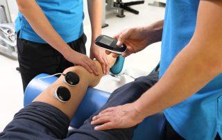 Rehabilitacja stawu kolanowego.Lekarz rehabilitant wykonuje zabieg na nodze pacjenta